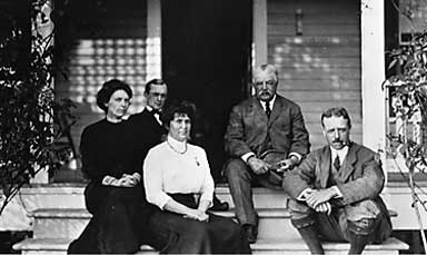 The Beadels on the front porch; center is Genevieve Beadel, at her right, Edward Beadel, and far right Henry Beadel with his ever present pipe. They are jointed by an unknown friend and their chauffeur at the left.
