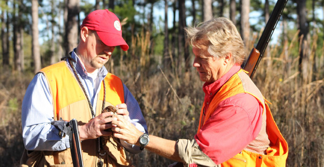 Dr. Terhune, at left, determines the age of a bird following harvest.