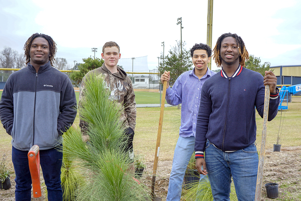 Students express their satisfaction after the hard work of planting a few of the larger longleaf pines included for instant structure.