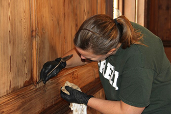 IFACS Chief Conservator Mary Aldrich restores historic wood paneling in the Dixie House living room. Tall Timbers hired IFACS to study and restore the historic finishes of the living room paneling. IFACS also cleaned the historic paneling in the library, gun room, bar, and master bedroom sitting area. Additionally, IFACS developed instructions for future care of the paneling.